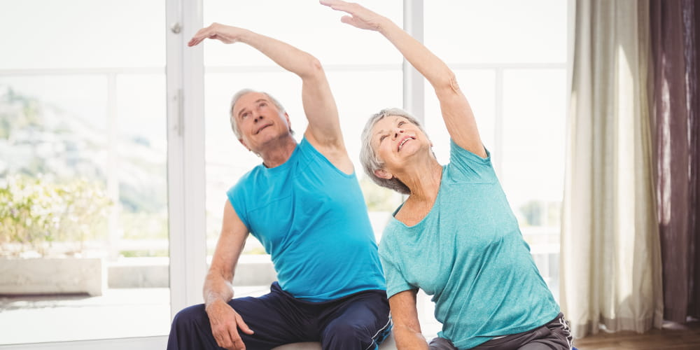 A importância da atividade física: casal da terceira idade fazendo exercícios.