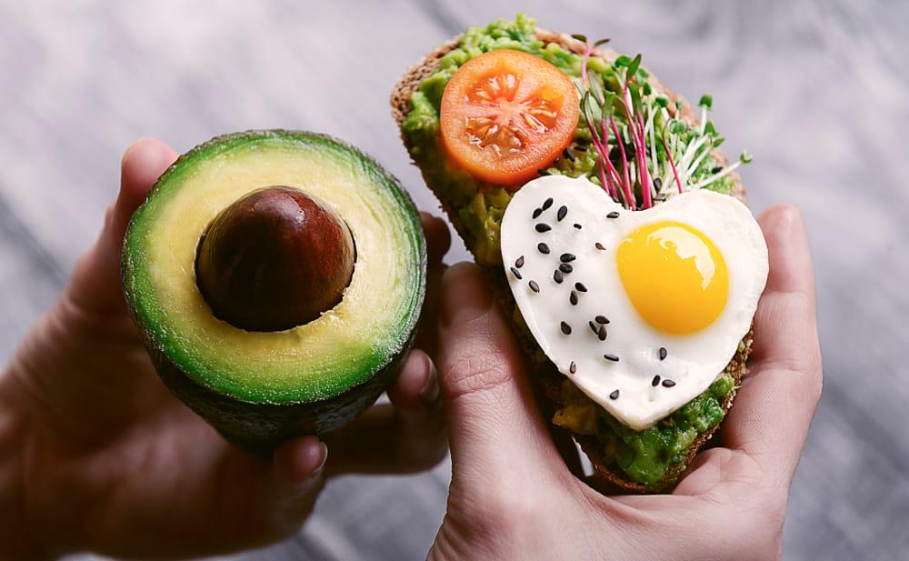 Alimentos que auxiliam na saciedade: mulher segurando uma bruscheta de abacate com ovo em formato de coração.
