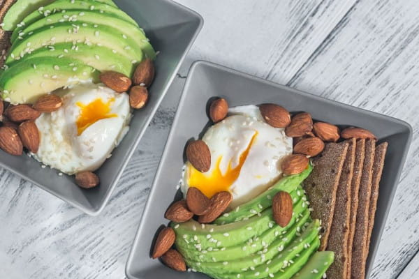 Alimentos que auxiliam na saciedade: prato com abacate, ovos e nozes.