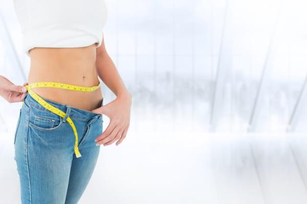Consulta Nutrição Online: mulher tirando medidas com a calça larga.