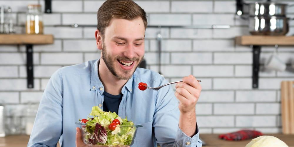 Emagrecimento e Manutenção do Peso: homem sorrindo fazendo sua refeição.