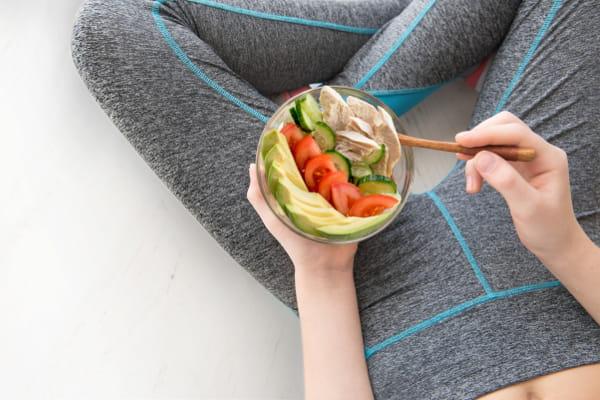 Emagrecimento e Manutenção do Peso: mulher sentada com seu prato de salada.