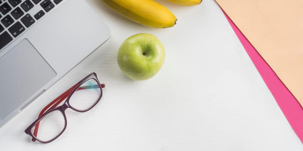 Nutrição Online: notebook ao lado de um óculos e uma banana.