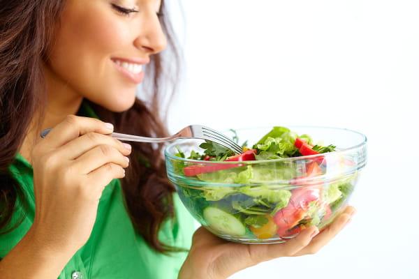 Nutrição Vegetariana: mulher com prato de salada na mão.