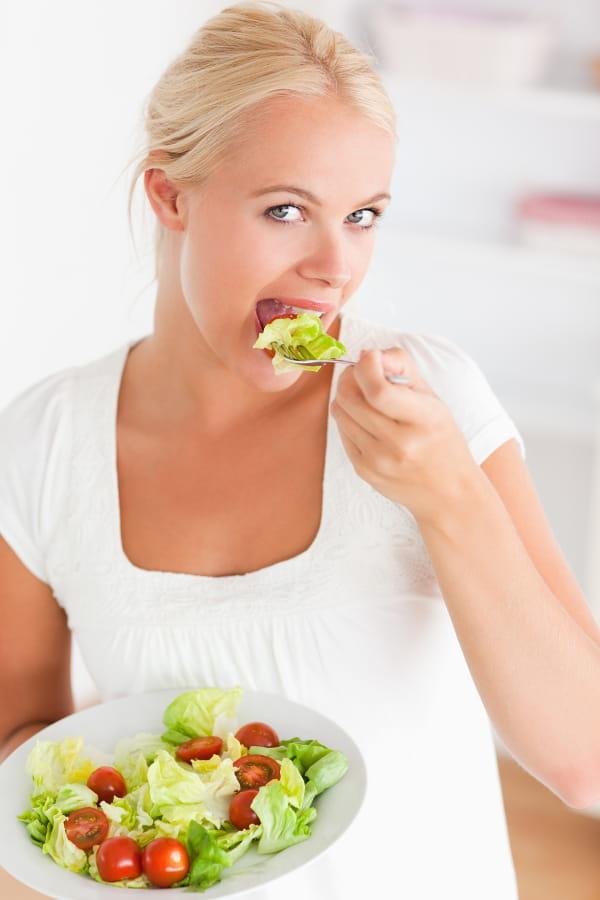 Mulher comendo uma uma prato com saladas.